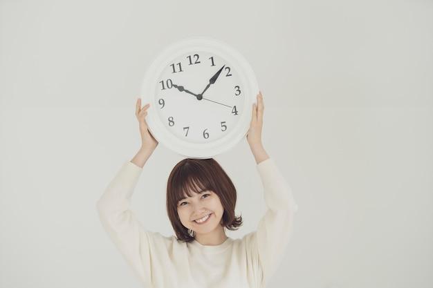 Mulher jovem asiática sorridente segurando o relógio de parede branco na cabeça