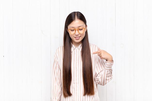 Mulher jovem asiática sorrindo alegre e casualmente, olhando para baixo e apontando para o peito