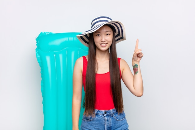 Mulher jovem asiática sorrindo alegre e feliz, apontando para cima com uma mão para copiar o espaço. conceito de verão