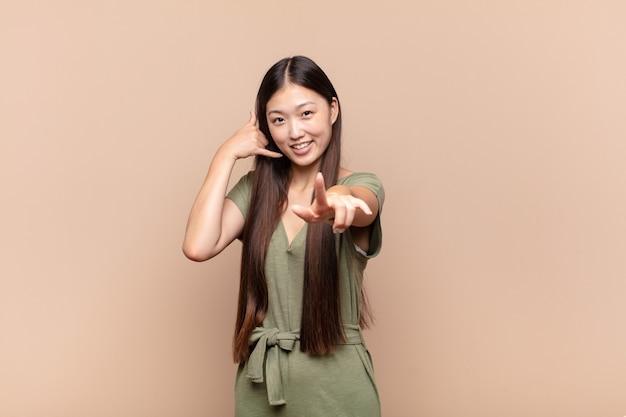 Mulher jovem asiática sorrindo alegremente e apontando para a câmera enquanto faz um gesto depois de ligar para você, falando ao telefone