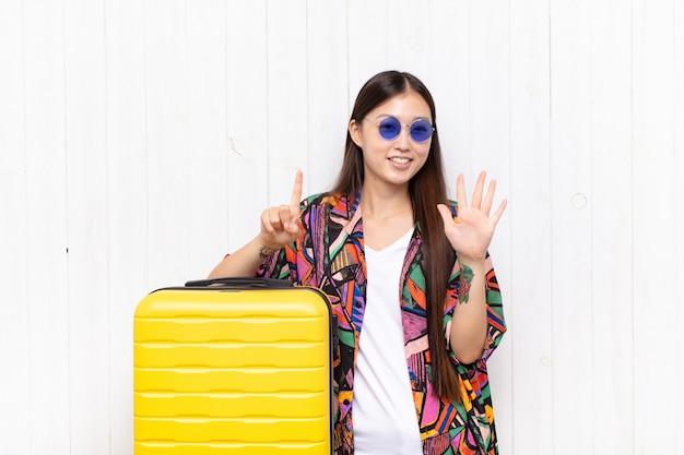 Mulher jovem asiática sorrindo e parecendo amigável, mostrando o número seis ou sexto com a mão para a frente, em contagem regressiva. conceito de férias
