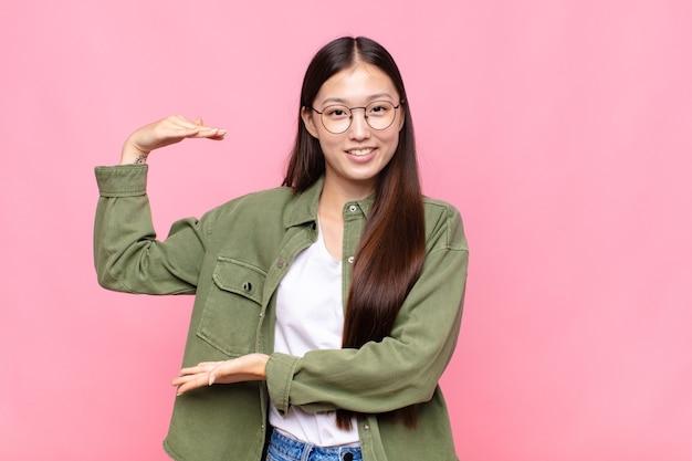 Mulher jovem asiática sorrindo, sentindo-se feliz, positiva e satisfeita, segurando ou mostrando um objeto ou conceito no espaço da cópia