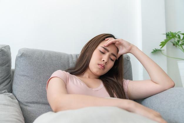 Mulher jovem asiática tocando sua cabeça, sentindo dor de cabeça enquanto está sentado no sofá da sala.