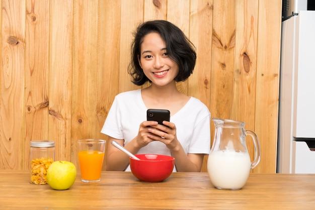 Mulher jovem asiática tomando café da manhã enviando uma mensagem ou e-mail com o celular
