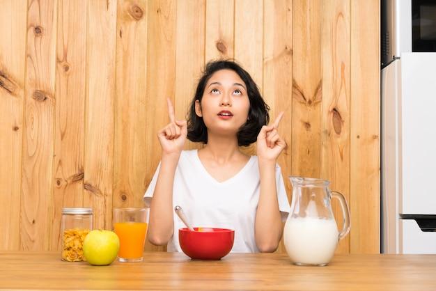 Mulher jovem asiática tomando café da manhã leite apontando com o dedo indicador uma ótima idéia