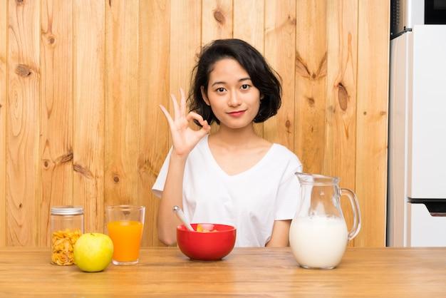 Mulher jovem asiática tomando café da manhã leite mostrando um sinal de ok com os dedos