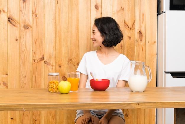 Mulher jovem asiática tomando café da manhã leite olhando para o lado
