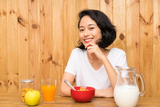 Mulher jovem asiática tomando café da manhã leite rindo