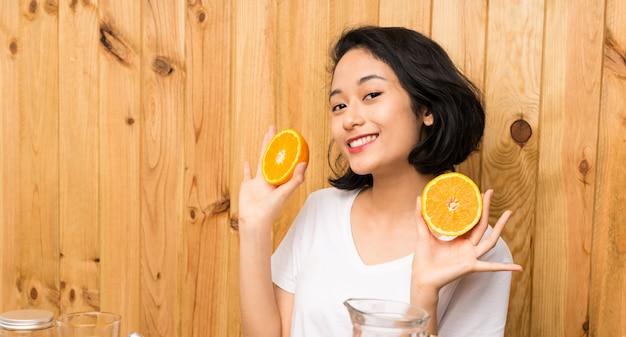 Mulher jovem asiática tomando café da manhã segurando uma laranja
