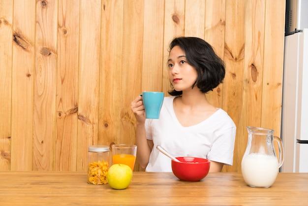 Mulher jovem asiática tomando café da manhã segurando uma xícara de café