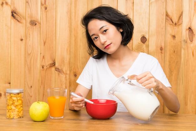 Mulher jovem asiática tomando café da manhã