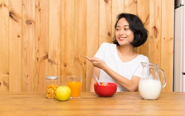 Mulher jovem asiática tomando leite do café da manhã, estendendo as mãos para o lado para convidar para vir