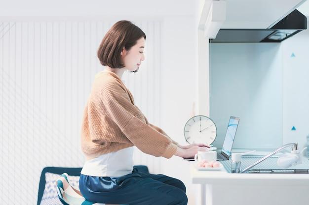 Mulher jovem asiática trabalhando remotamente na sala de casa