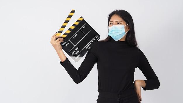 Mulher jovem asiática usa máscara facial ou máscara médica e claquete preto com preensão para as mãos