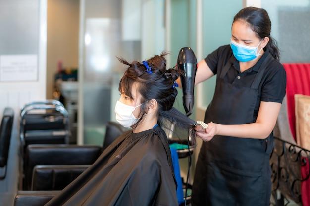 Mulher jovem asiática usando máscaras para proteger-se de covid-19 durante cabeleireiro usando secador de cabelo e pente para cabelos pretos no salão de beleza.