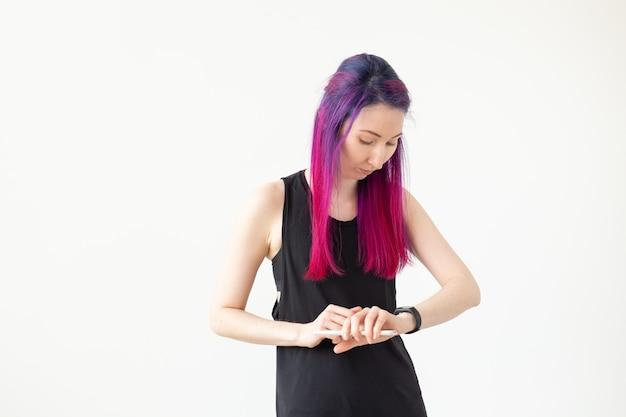 Mulher jovem asiática usando o rastreador de atividade dentro de casa.