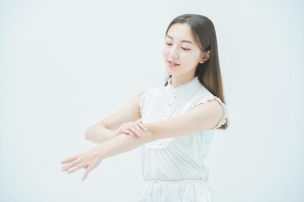 Mulher jovem asiática verificando as condições da pele dos braços