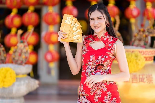 Mulher jovem asiática vestindo um cheongsam vermelho tradicional chinês, segurando envelopes amarelos com o texto em chinês