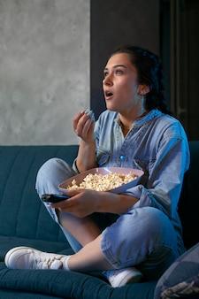 Mulher jovem assistindo serviço de streaming em casa