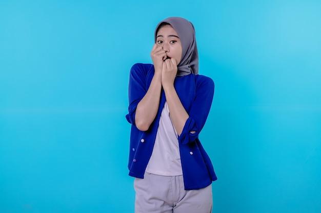 Mulher jovem assustada, chocada e espantada usando hijab, gritando e tremendo, cobrindo com as mãos