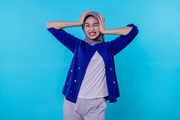 Mulher jovem assustada, chocada e surpresa, usando hijab, gritando e segurando a cabeça com as mãos