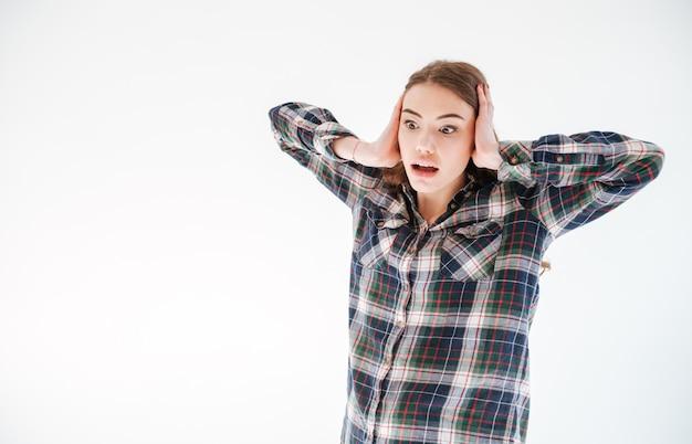 Mulher jovem assustada com medo em pé de camisa xadrez e gritando