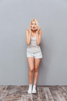 Mulher jovem assustada em pé com a boca aberta sobre uma parede cinza