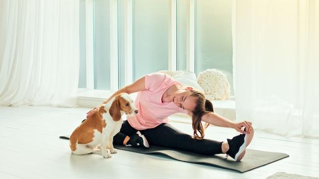 Mulher jovem ativa aquecendo fazendo exercícios de flexão lateral em uma esteira de ginástica em casa