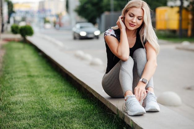 Mulher jovem ativa vestindo roupas esportivas e relógio inteligente no pulso, descansando após andar de bicicleta ao ar livre. loira saudável e em forma sentada na rua da cidade e olhando para baixo.