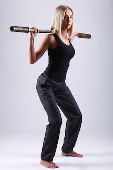 Mulher jovem atleta com barra de exercício