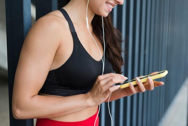 Mulher jovem atleta com um smartphone
