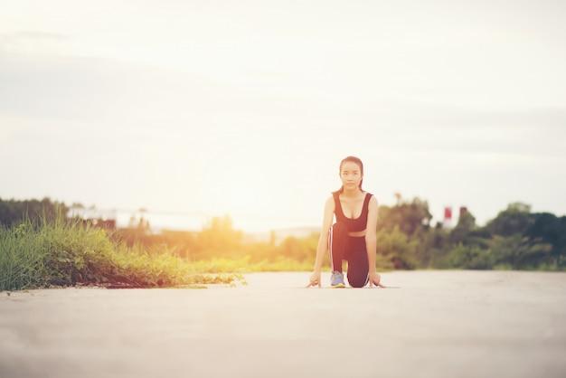 Mulher jovem atleta está pronta para começar a correr ou correr