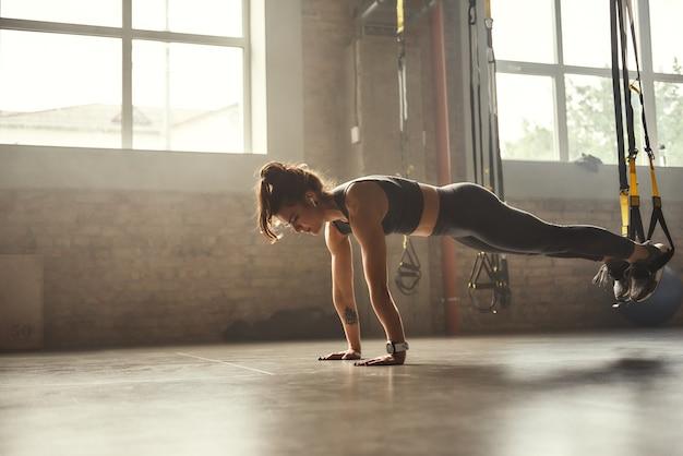 Mulher jovem atlética se exercitando com alças de suspensão em roupas esportivas, treinando pernas com trx