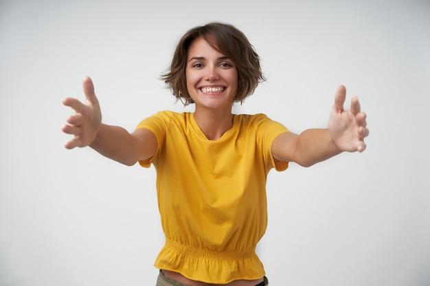 Mulher jovem atraente alegre com cabelo castanho curto em pé com os braços abertos, feliz em ver uma pessoa perto e gostaria de dar um abraço