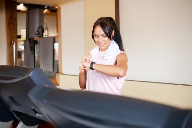 Mulher jovem atraente aptidão correndo na esteira, vestindo roupas esportivas brancas, mulher desportiva saudável, fazendo exercícios cardio na esteira