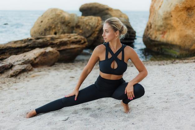 Mulher jovem atraente aptidão no sportswear fazendo perna esticando na areia antes de treinar na praia selvagem. treinamento esportivo. exercício ao ar livre