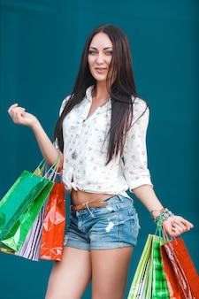 Mulher jovem atraente com sacos de compras ao ar livre