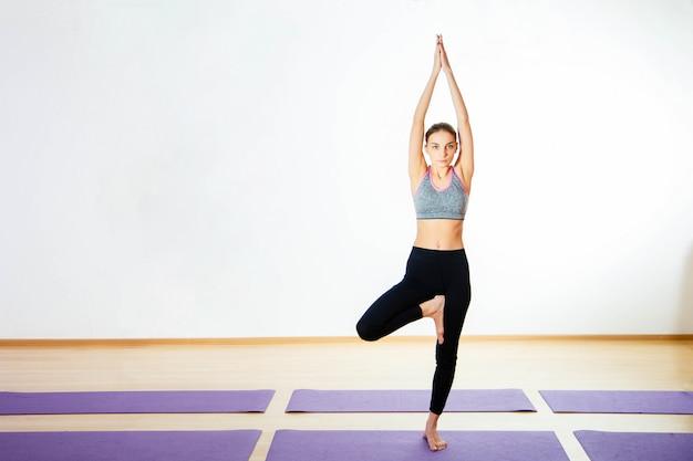 Mulher jovem atraente desportiva no sportswear fazendo exercício para espinha