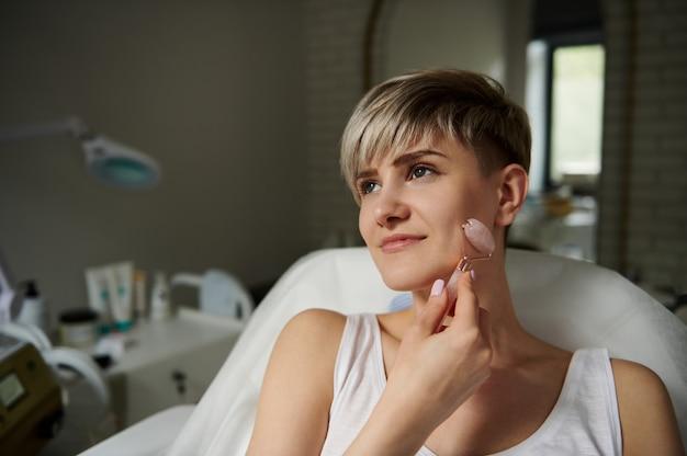 Mulher jovem atraente e sorridente, massageando o rosto ao longo do contorno. realização de massagem de drenagem linfática com massageador de rolos com pedras de jade. fechar-se