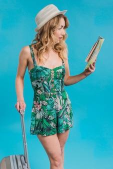 Mulher jovem atraente espantada no vestido e chapéu segurando o mapa e a mala