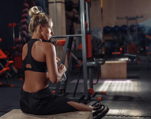 Mulher jovem atraente esporte no sportswear descansando entre conjuntos de treino no ginásio