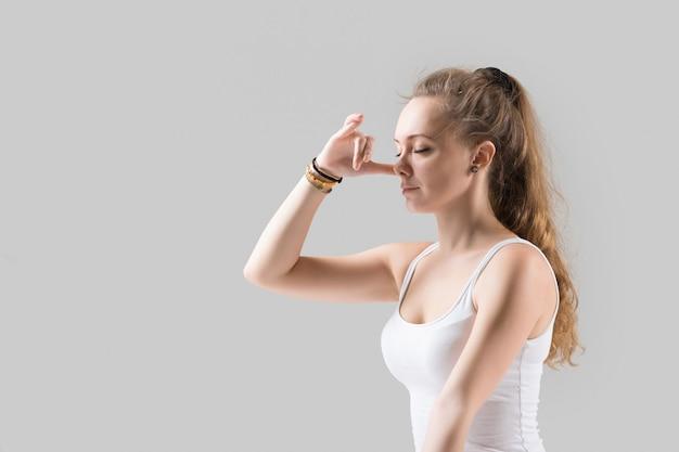 Mulher jovem atraente fazendo respiração alternativa de nostril, cinza