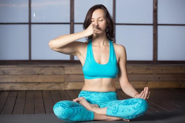 Mulher jovem atraente fazendo respiração alternativa de nostril, studi
