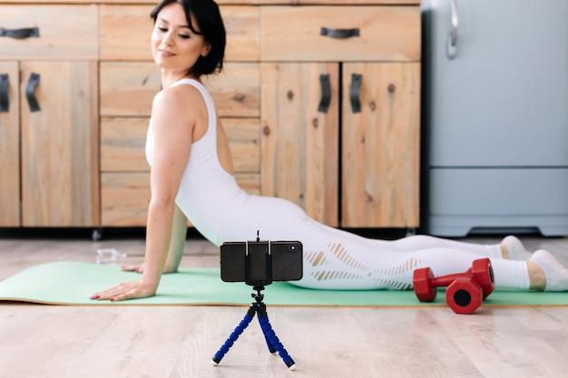 Mulher jovem atraente fitness vestindo roupas esportivas, fazendo exercícios de alongamento, usando o tapete de fitness