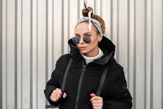 Mulher jovem atraente hippie com penteado elegante com uma bandana de óculos pretos em um longo casaco preto com uma mochila nos ombros se passando perto de uma parede de metal. menina estilosa.