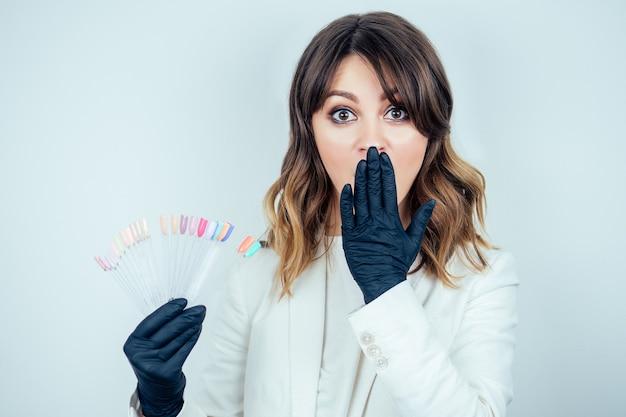 Mulher jovem atraente manicure profissional (mestre da manicure) em uma jaqueta branca e luvas de borracha preta possui uma paleta de cores de esmaltes em um salão de beleza spa em um fundo branco.