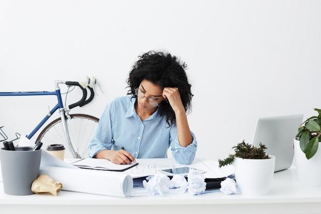 Mulher jovem atraente, mestiça, de óculos redondos, absorta no processo de trabalho
