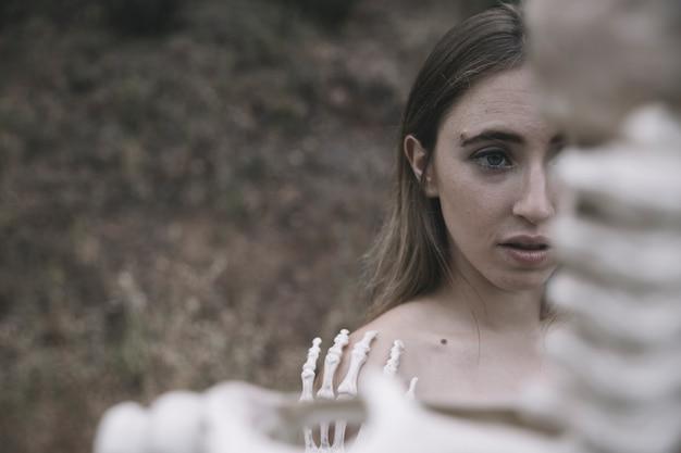 Mulher jovem, atrás de, ossos