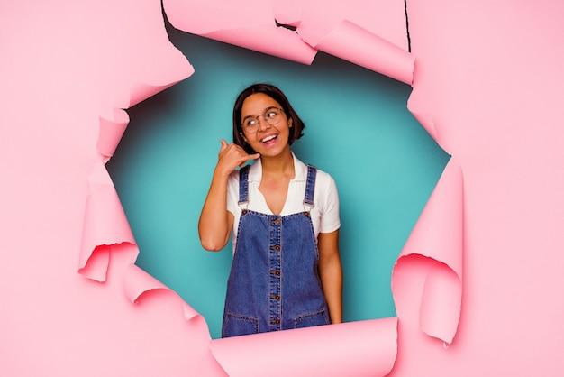 Mulher jovem atrás de uma parede quebrada fazendo gestos de telefone com as mãos