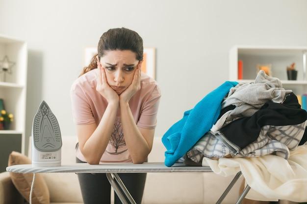 Mulher jovem atrás de uma tábua de passar roupas com roupas na sala de estar